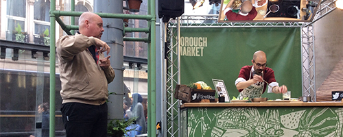 Photograph of signer Ben interpreting a demonstration kitchen at Borough Market